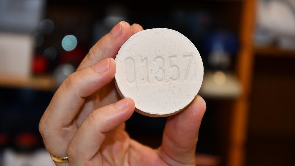 Ein feuerfester Stein mit einer fünfstelligen Nummer liegt in einer Hand. Es ist ein Identitätsstein, der mit in den Ofen kommt und sicherstellen soll, dass die Asche in die vorgesehene Urne kommt.