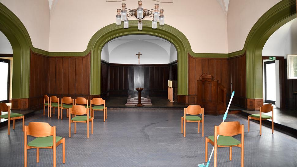 Der Blick in eine Halle mit Deckenbögen. Vereinzelt stehen Stühle herum, vorne steht ein Wischer.