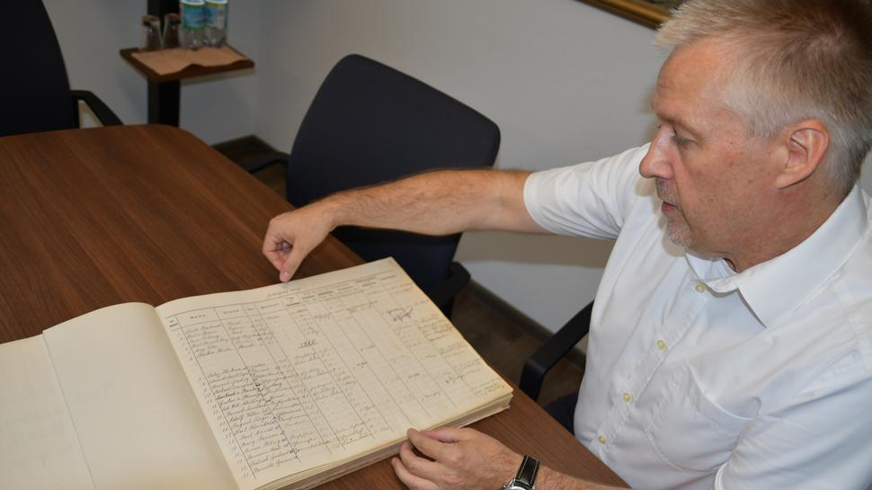 Krematoriums-Geschäftsführer Frank Geyer sitzt auf einem Stuhl und öffnet das erste Aschenbeisetzungs-Buch des Friedhofs aus dem Jahr 1909.