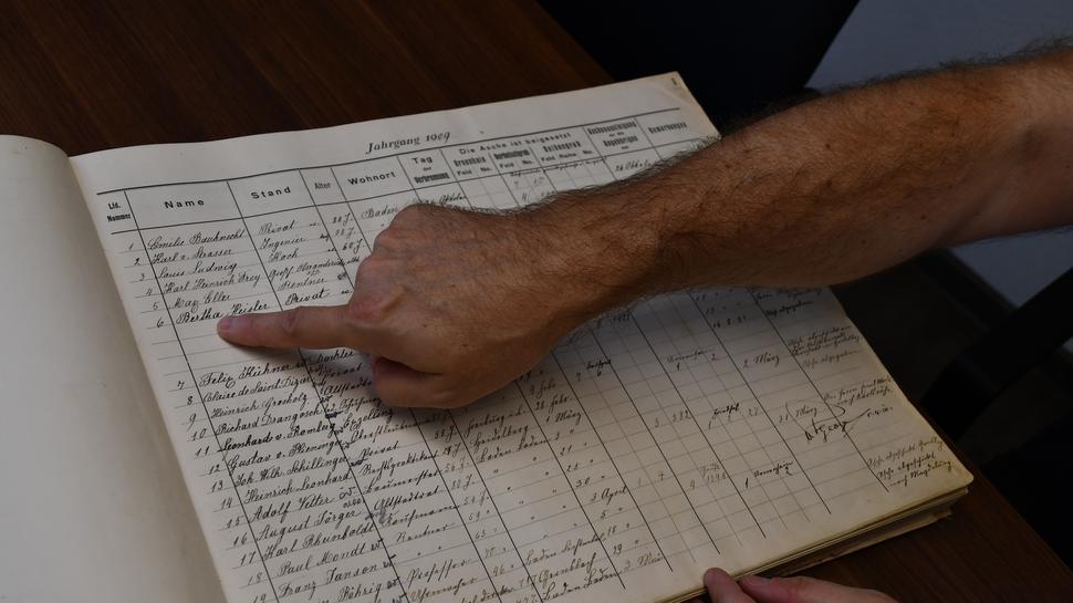 Eine Hand liegt auf einem handgeschriebenen Buch. Mit dem Finger zeigt ein Mann auf den sechsten Eintrag.