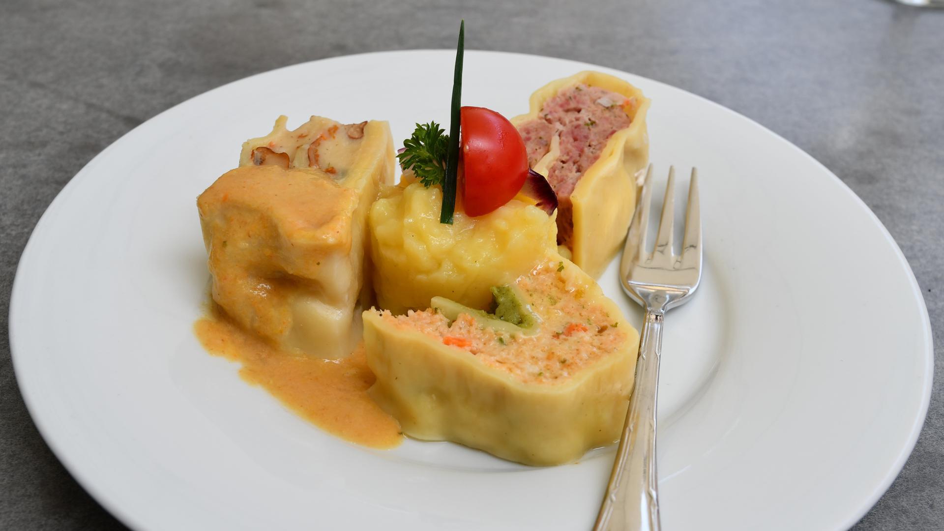 Auf einem Teller sind drei Sorten Maultaschen angerichtet. Verziert sind sie mit einem Klecks Kartoffelsalat, Petersilie und einer halben Cocktailtomate.