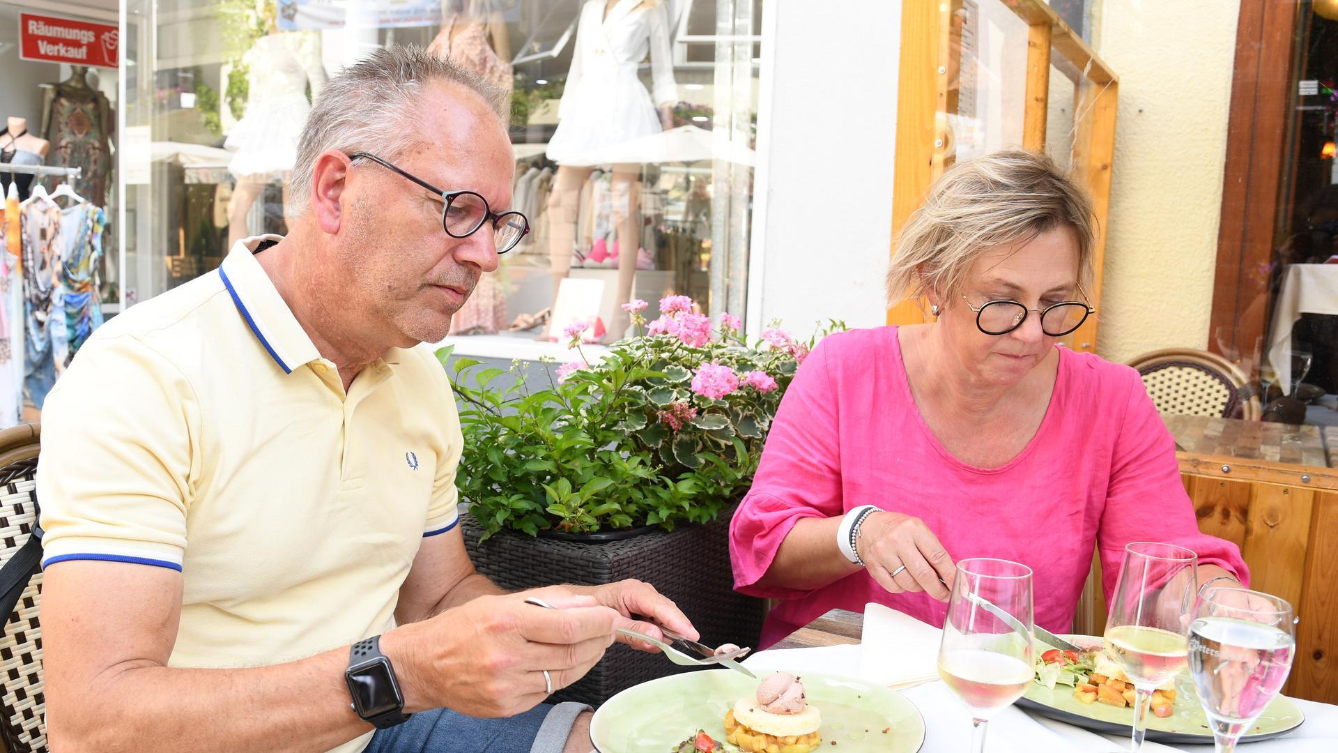 Ein Mann und eine Frau sitzen am Tisch und essen.