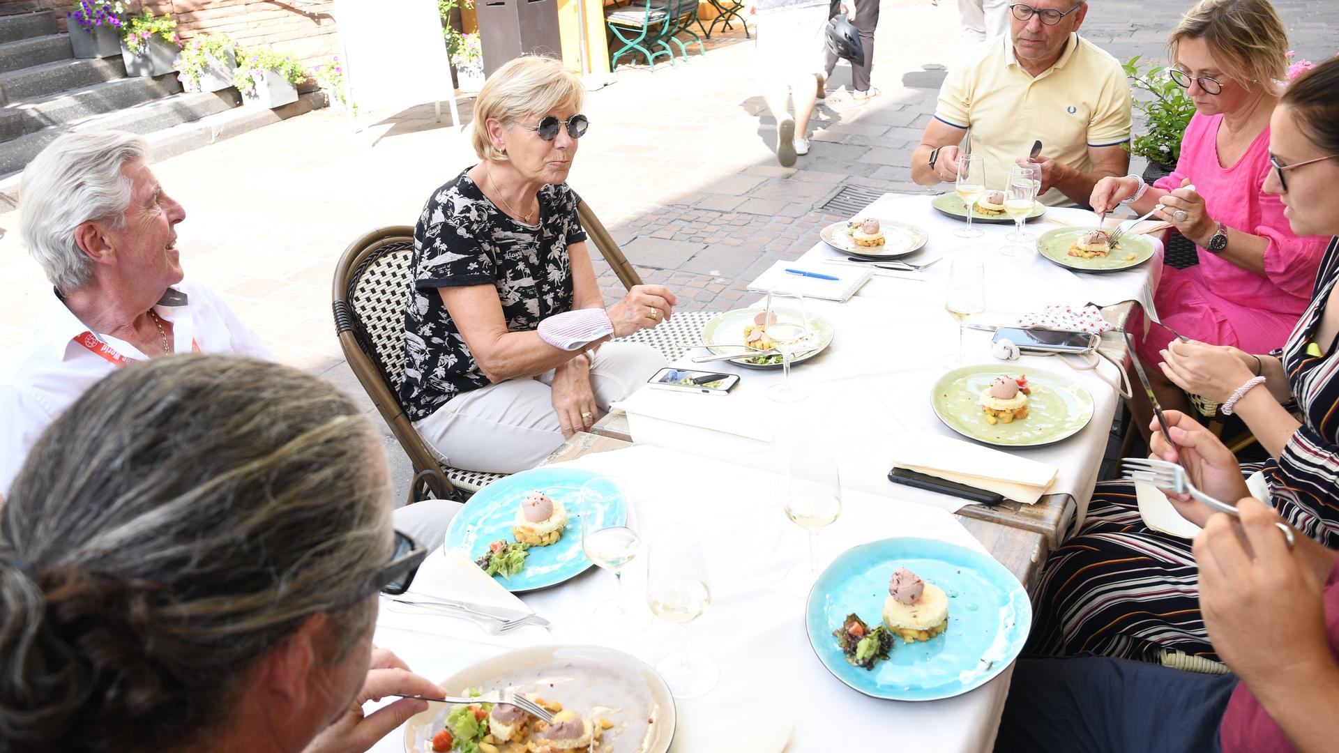 Mehrere Personen sitzen an einem gedeckten Tisch und essen Entenlebermousse und warmen Apfelsalat.