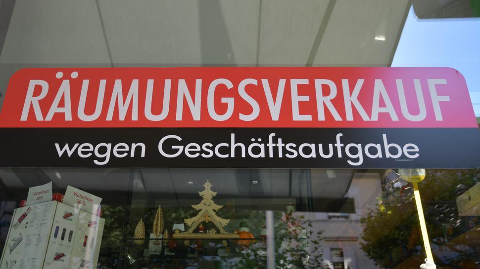 An einer Schaufensterscheibe klebt ein rotes Schild: Räumungsverkauf wegen Geschäftsaufgabe.