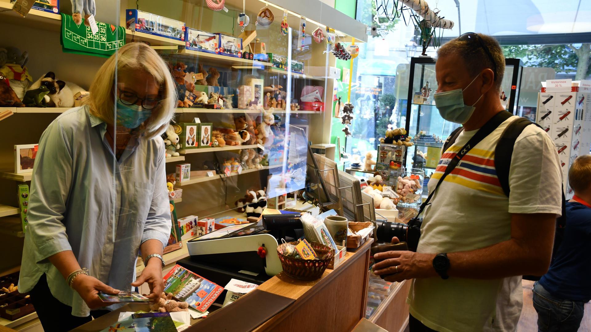 Ein Tourist mit Kamera um den Hals zückt seinen Geldbeutel. Die Verkäuferin wickelt seine Einkäufe ein.