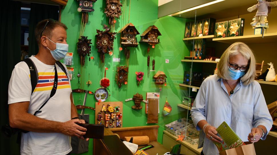 Ein Mann bezahlt ein Buch. Die Verkäuferin steckt es in eine Tüte. An der Wand hinter den beiden hängt eine Reihe voll Kuckucksuhren.
