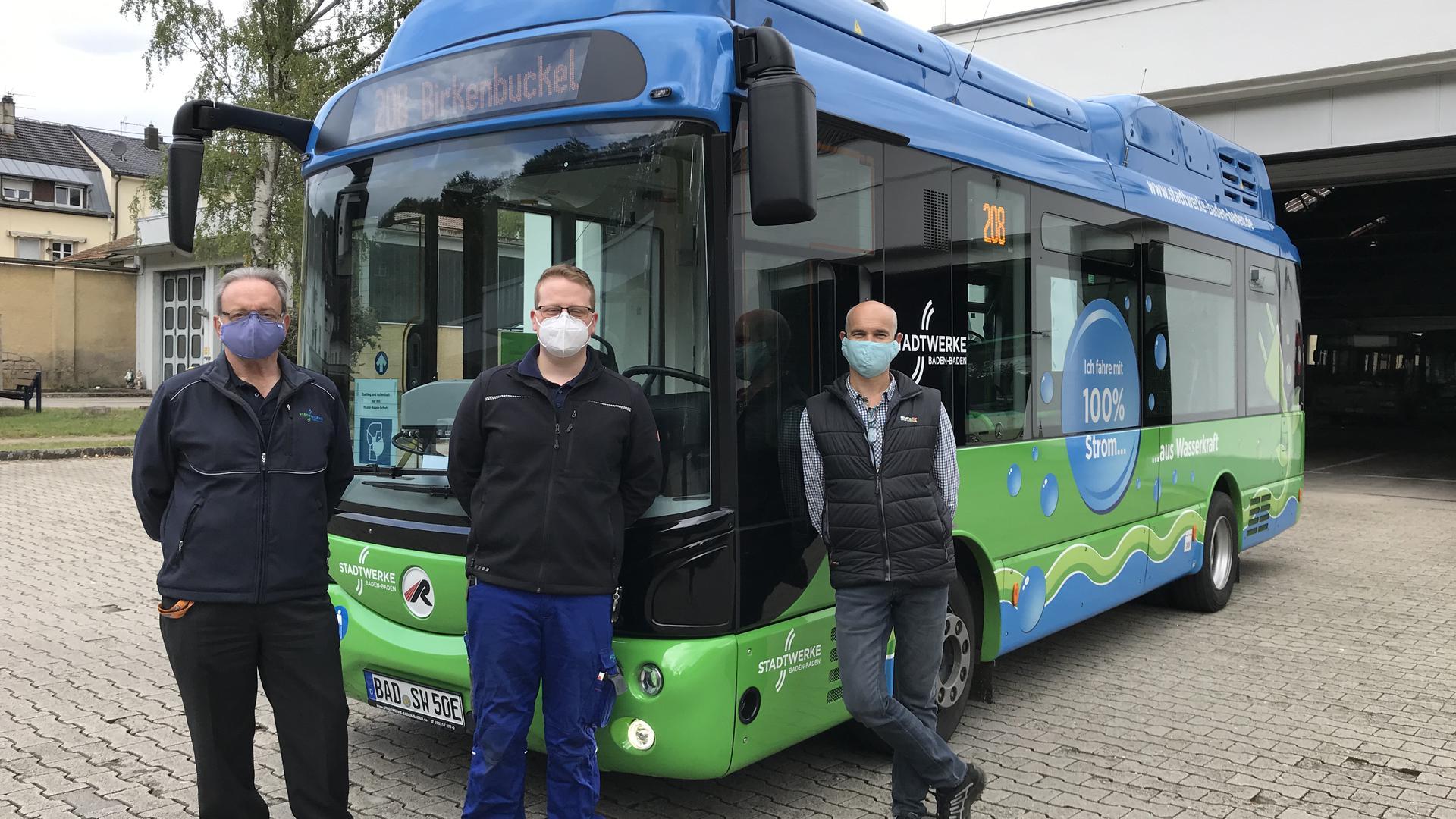 Fahrdienstleiter Patrick Lainé und die Werkstattmeister Sebastian Späth und Ralph Geiger stehen vor dem ersten E-Bus in Baden-Baden
