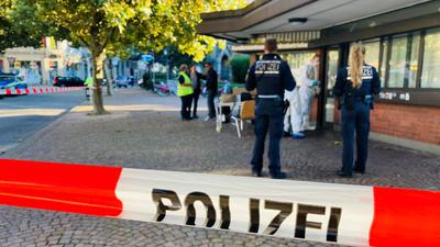 Flatterband der Polizei im Vordergrund, dahinter Polizisten.