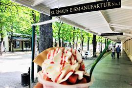 Ein Genießer hält einen Eisbecher ins Bild. Im Hintergrund sind die Kurhaus-Kolonnaden in Baden-Baden mit der Kastanienallee zu sehen.