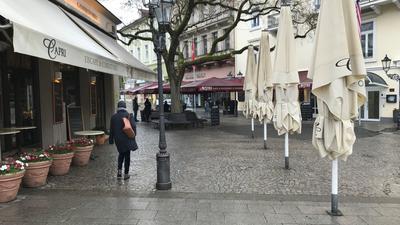 Eine Frau geht bei Regen durch die Innenstadt. Im Hintergrund ist ein Café mit weißen Markisen und Schirmen zu sehen sowie ein Restaurant mit roten Markisen.