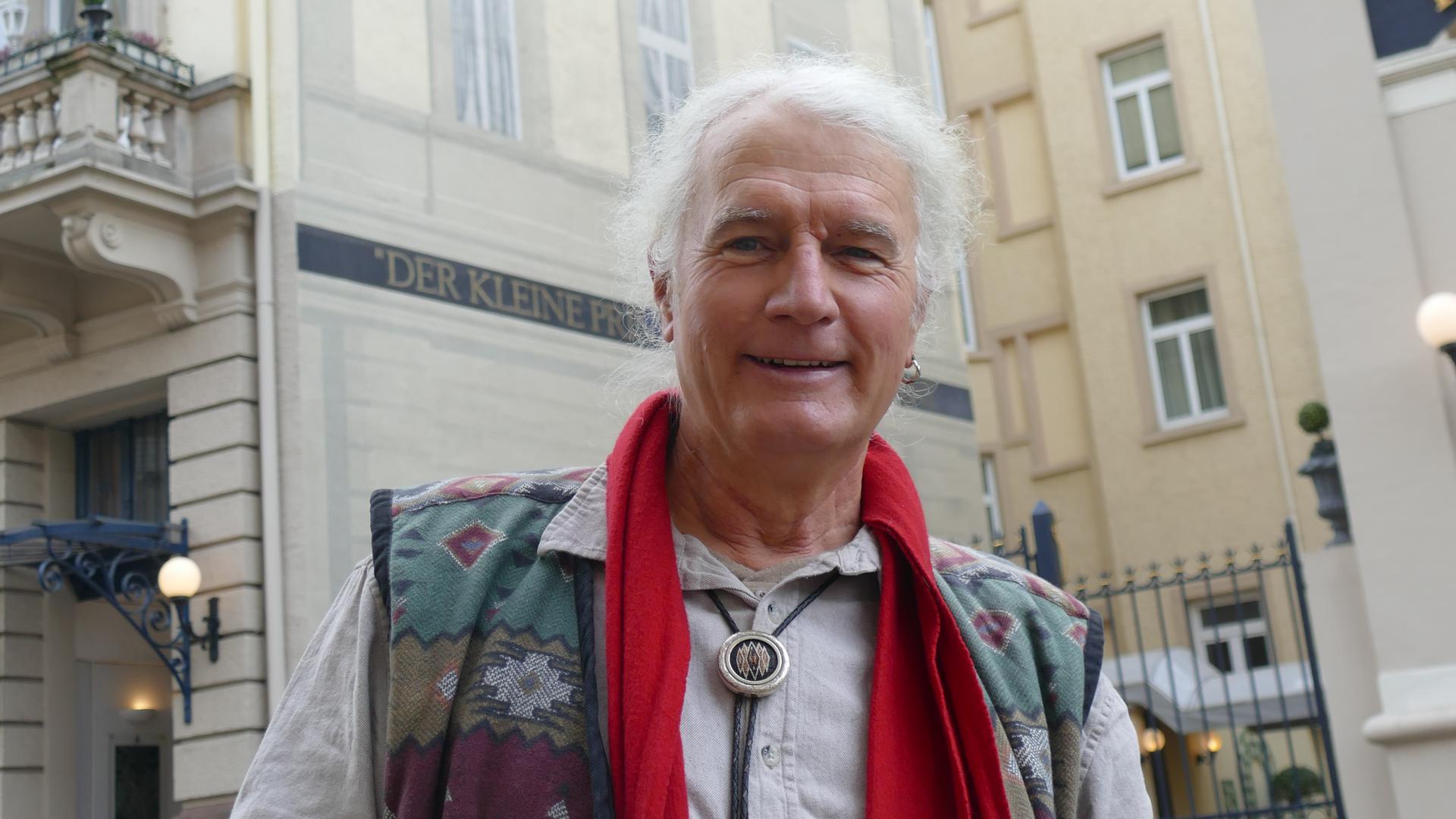Künstler Bernd Krause steht vor seinem Fassadengemälde am Hotel Der kleine Prinz