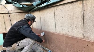 Ein Steinmetz verstreicht mit einer Kelle den Putz auf der Brüstung der Fieser-Brücke in Baden-Baden