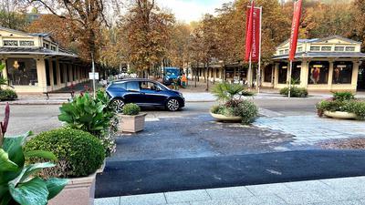 Ein Auto fährt durch die Kaiserallee zwischen Fieser-Brücke und Kurhaus-Kolonnaden.