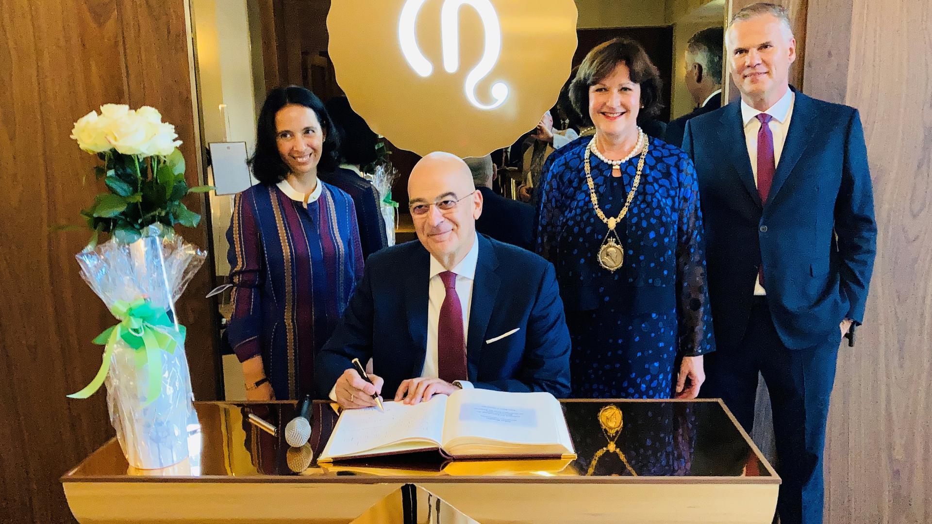 Der griechische Außenminister Nikos Dendias trägt sich in das Goldene Buch der Stadt Baden-Baden ein. Dahinter stehen Vasilika Basia (links), Oberbürgermeisterin Margret Mergen und Jörg Rockenhäuser.