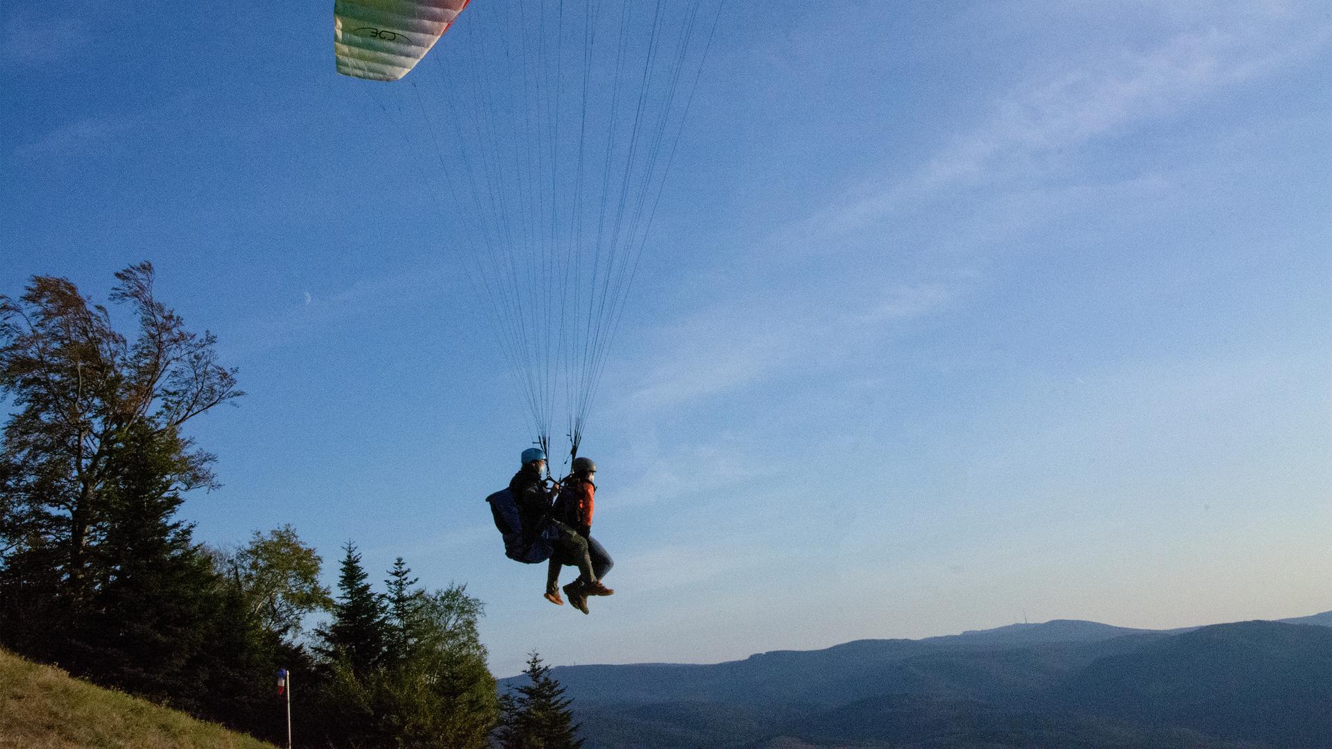 Marc Kadalla und Catrin Dederichs schweben mit einem Gleitschirm den Berg Merkur hinab.