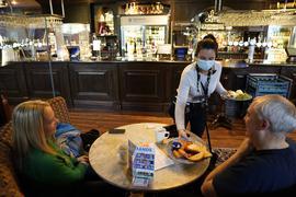 Eine Kellnerin bringt zwei Gästen in einem Pub in Newcastle eine Mahlzeit an den Tisch.