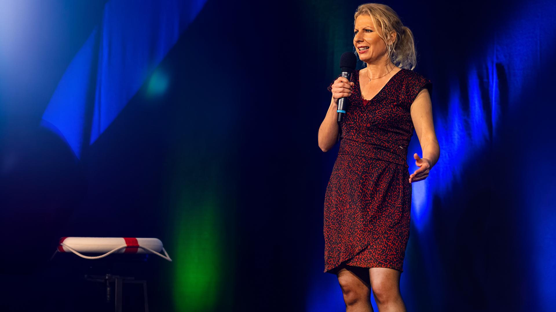 Corinna Spaeth steht auf der Bühne bei einem Speaker Slam, neben ihr liegt ein Rettungsring.