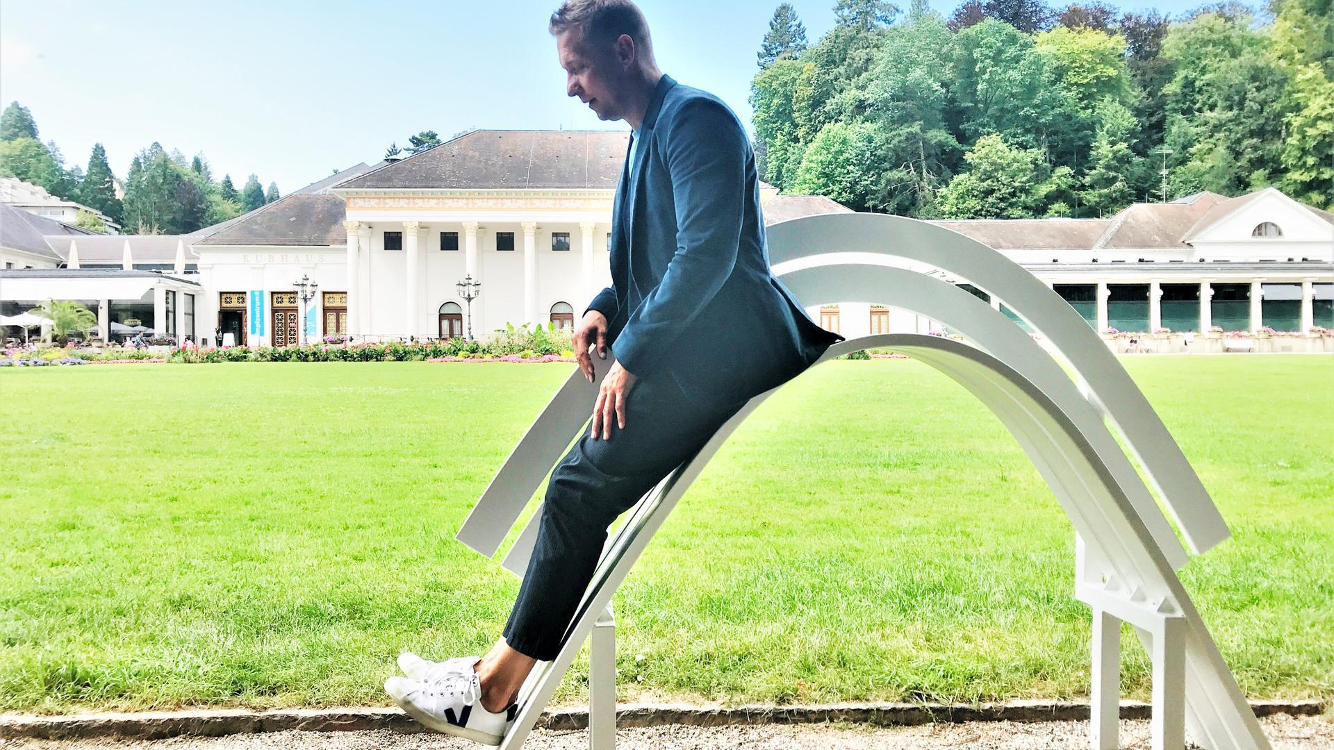 """Der dänische Künstler Jeppe Hein nutzt im Kurgarten in Baden-Badeneine seiner Modified Social Benches"""",  modifizierte soziale Bänke, für eine Rutschpartie."""