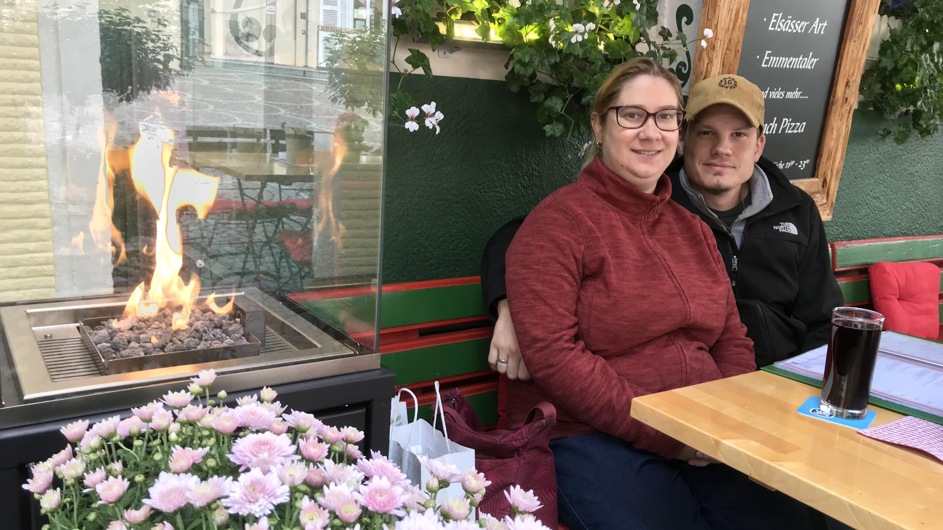 Ein Pärchen sitzt im Restaurant Laterne Baden-Baden draußen neben einem Heizofen.