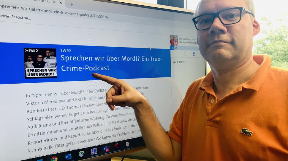 """Moderator Holger Schmidt steht vor einem Monitor. Auf dem Bildschirm wird auf die Podcast-Reihe """"Sprechen wir über Mord?!"""" hingewiesen."""
