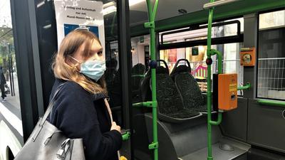 Eine junge Frau steigt mit Mund- und Nasenschutz in einen Bus der Verkehrsbetriebe Baden-Baden ein.