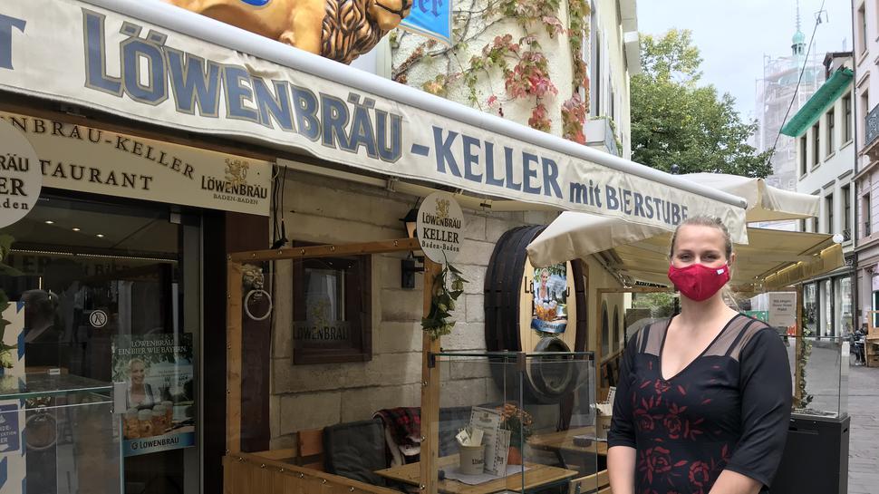 Isabel Bülow steht vor dem Baden-Badener Löwenbräu-Keller neben einem Heizofen und einer Trennwand