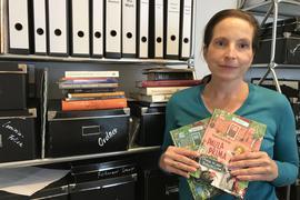 Die Drehbuchautorin Regine Bielefeldt steht vor einem Regal voller Ordner, sie hält ihre Kinderbücher in der Hand.