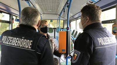 Zwei Männer der Polizeibehörde reden mit einer Frau, die eine Maske trägt, in einem Bus in Baden-Baden