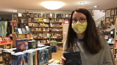 """Tanja Eger von der Buchhandlung Mäx & Moritz in Baden-Baden hält das Buch """"Sankt Irgendwas"""" hoch."""