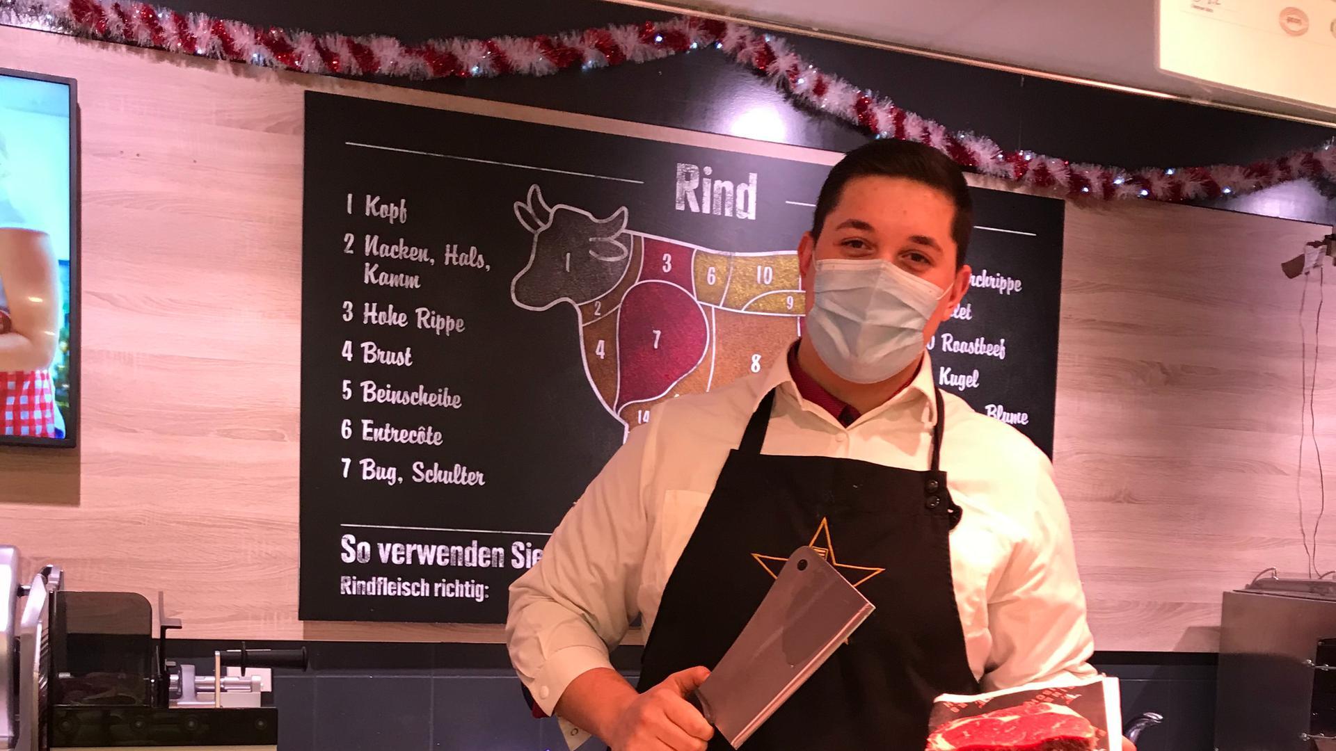 Der Fleischereifachverkäufer Adrian Stanciu hält ein Messer und ein Stück Fleisch in der Hand.
