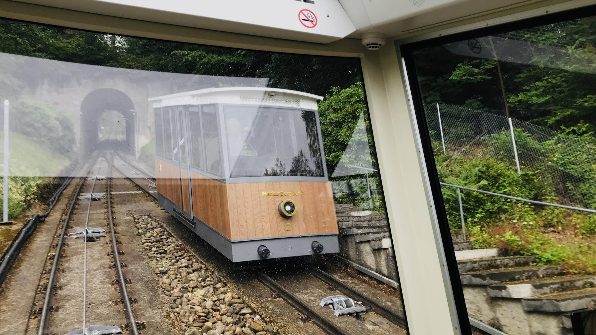 Die Merkurbergbahn passiert auf der Bergfahrt auf einem Ausweichgleis einen Wagen, der zur Talstation unterwegs ist.