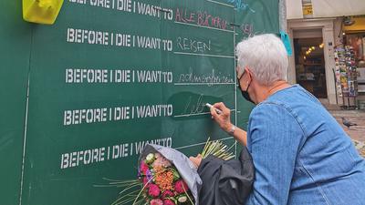 Frau schreibt auf Kreidetafel.