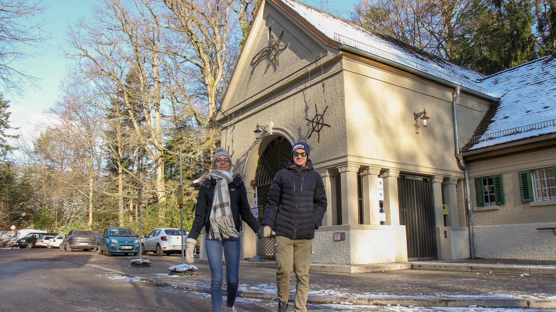 Ein Pärchen spaziert händchenhaltend vor der Talstation der Merkurbahn in Baden-Baden.