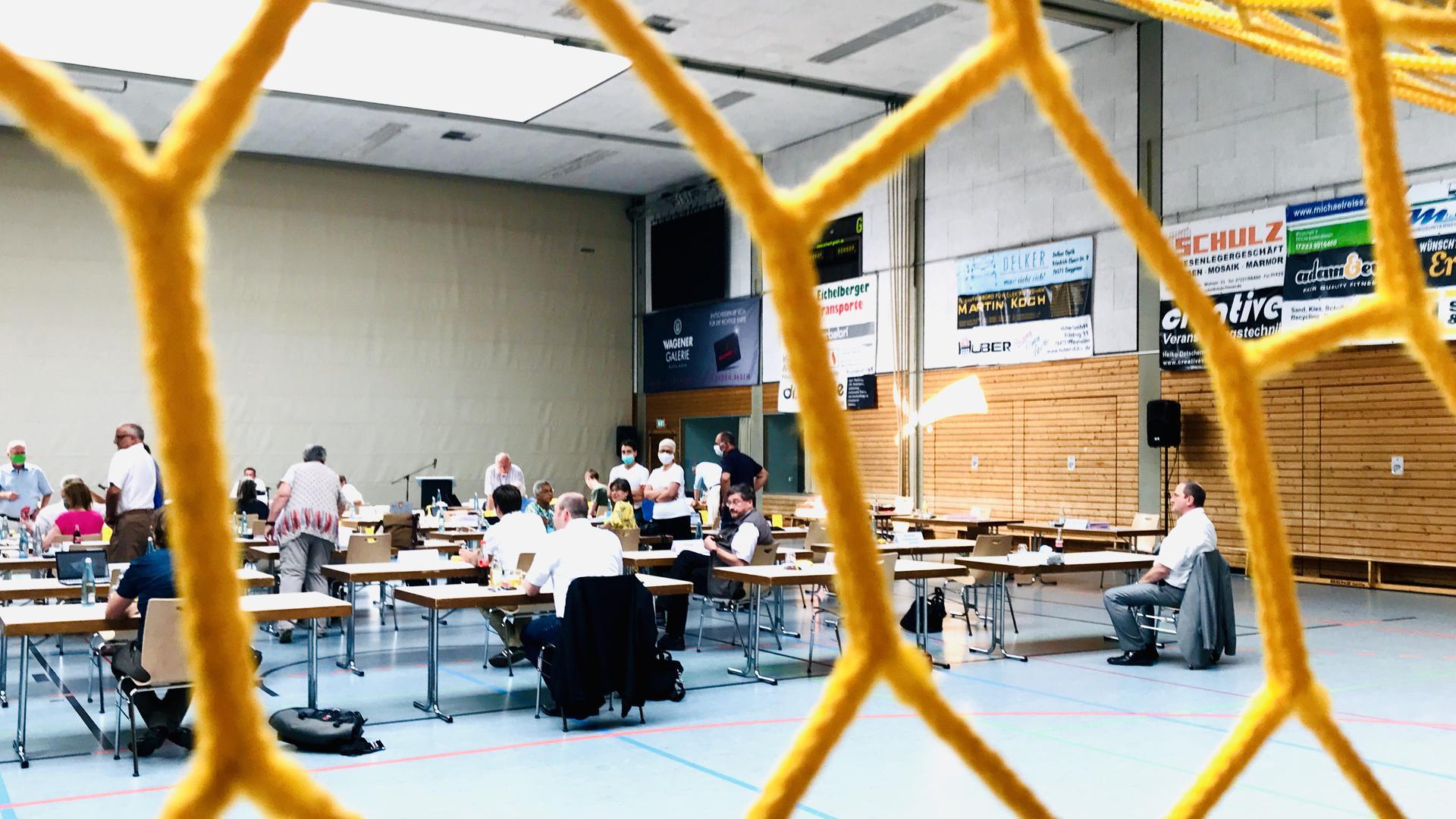 In einer Sporthalle stehen Tische und Menschen mit Mundschutzmasken unterhalten sich. An den Wänden hängen Werbebanner Der Gemeinderat Baden-Baden tagt in der Rheintalhalle Sandweier