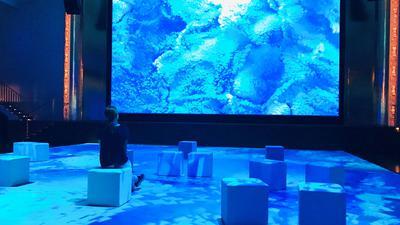 """Ein Frau sitzt auf einem Hocker im Bénazetsaal des Kurhauses Baden-Baden. Der Bodenbelag und ist eine große Projetionsfläche, Auch auf der Bühne hängt eine große Leinwand. Das Werk """"Bosphorus"""" des Medienkünstlers Refik Anadol lässt Besucher ins Marmarameer am Bosporus eintauchen. Die Bewegungen des Meeres sind durch über 30 Tage gesammelte Hochfrequenz-Radardaten des türkischen Wetterdienstes zu erleben."""