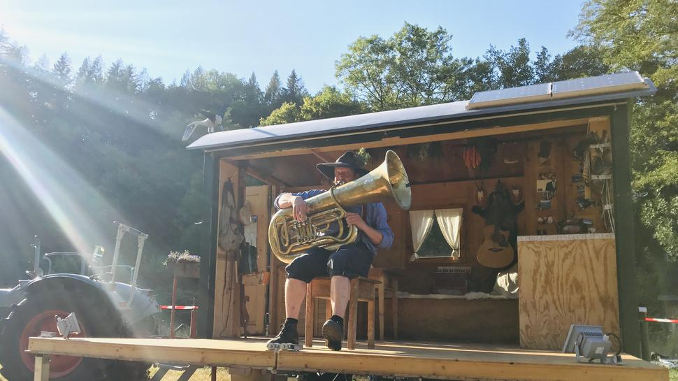 Eine Mann sitzt auf einer Holzbühne auf einem Schemel und spielt Tuba.