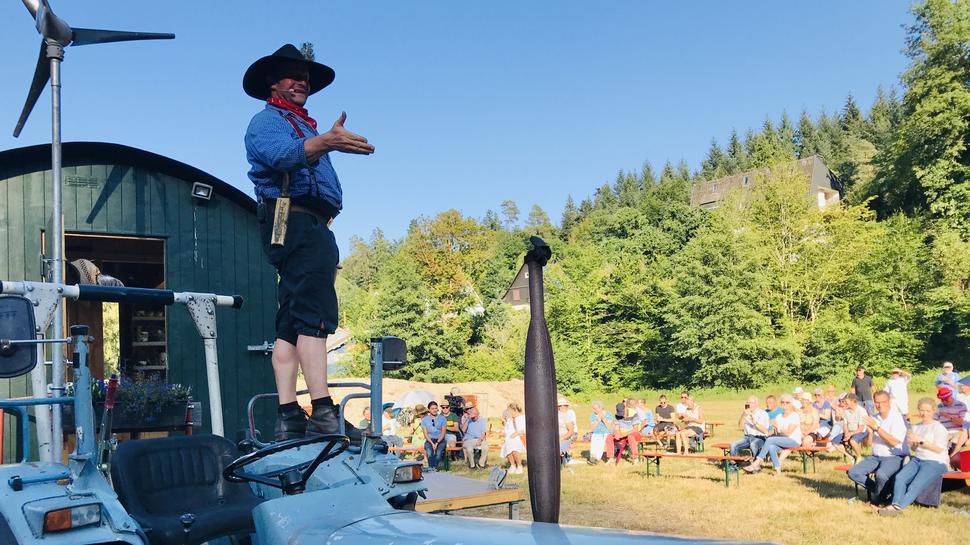 Ein Künstler steht auf einem Traktor und spricht zu seinem Publikum, das auf Festbänken sitzt.