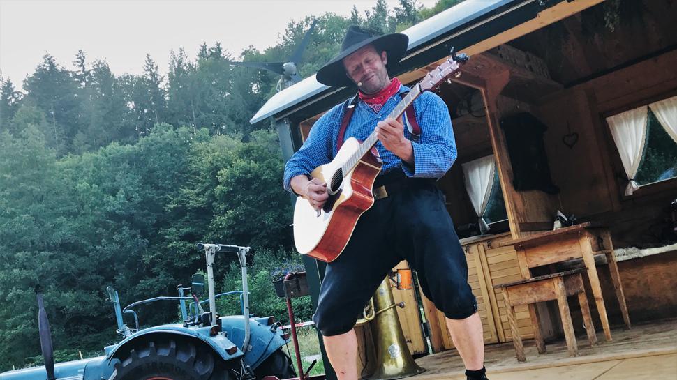 Ein Mann steht mit einer Gitarre auf einer Holzbühne. Es ist eine ausgeklappte Seitenwand eines umgebauten ehemaligen Forstwagens.
