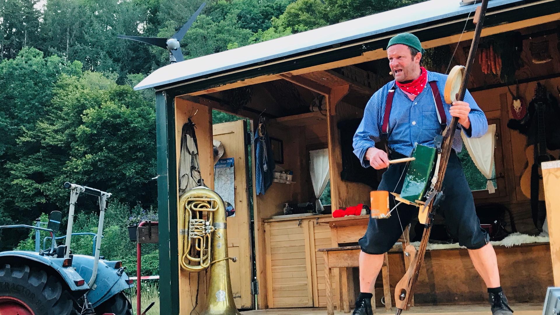 Ein Mann steht mit einem Holzstab auf einer Holzbühne. Am Stab hängen Blechdosen und ein kleines Tamburin, die als Percussionsinstrumente genutzt werden.