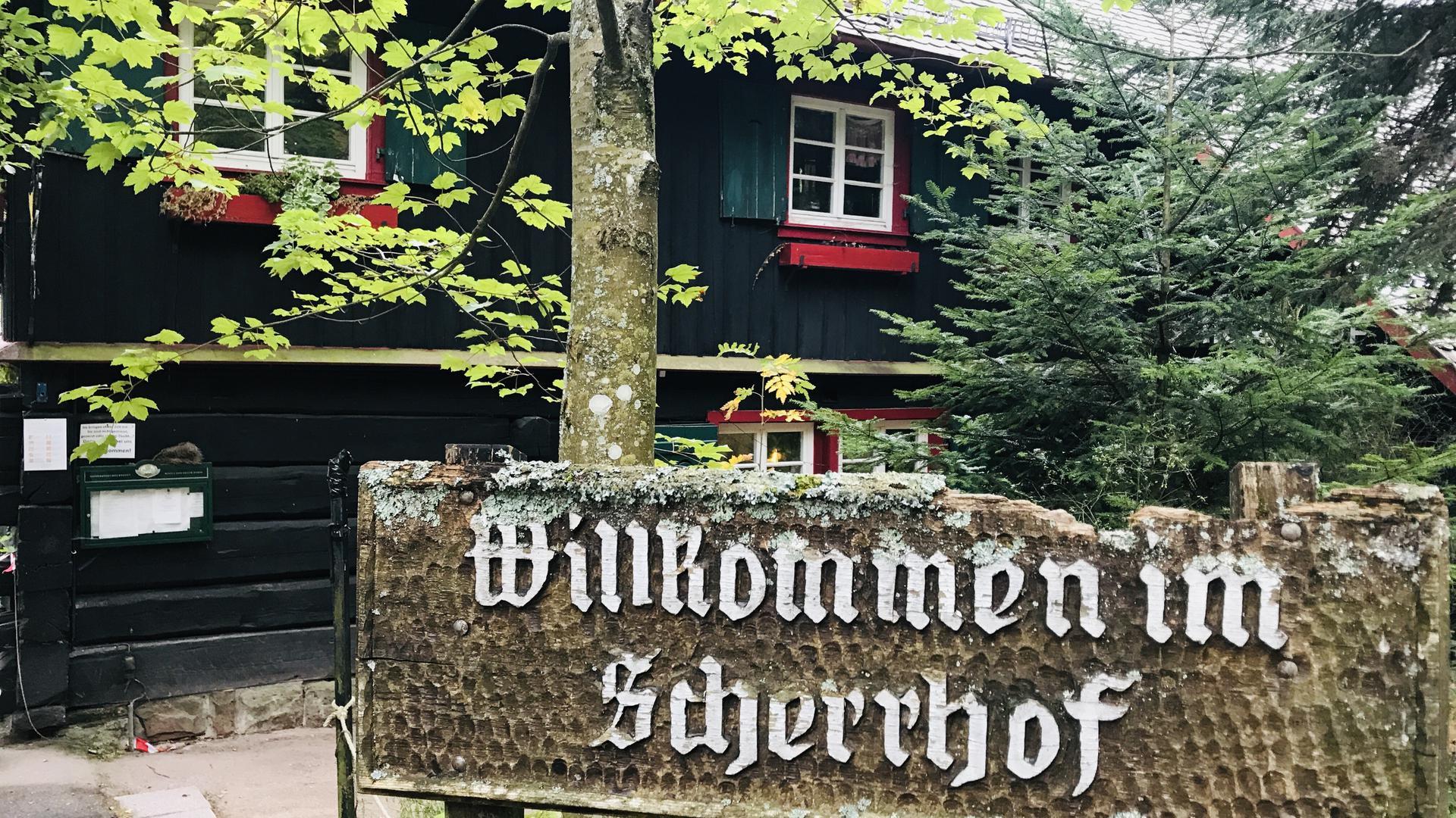 """Vor einem Holzgebäude weist ein Schild mit der Aufschrifft """"Willkommen im Scherrhof"""" auf das Ausflugslokal im Stadtwald Baden-Baden hin."""