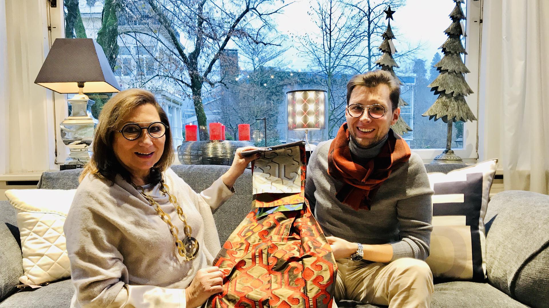 Die Inneneinrichtungsexperten Iris Piening und ihr Sohn Roger sitzen mit Mustern von hochwertigen Dekostoffen auf einem Designersofa.