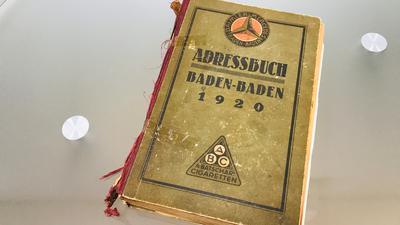 Ein Adressbuch von Baden-Baden aus dem Jahr 1920 liegt auf einem Glastisch.
