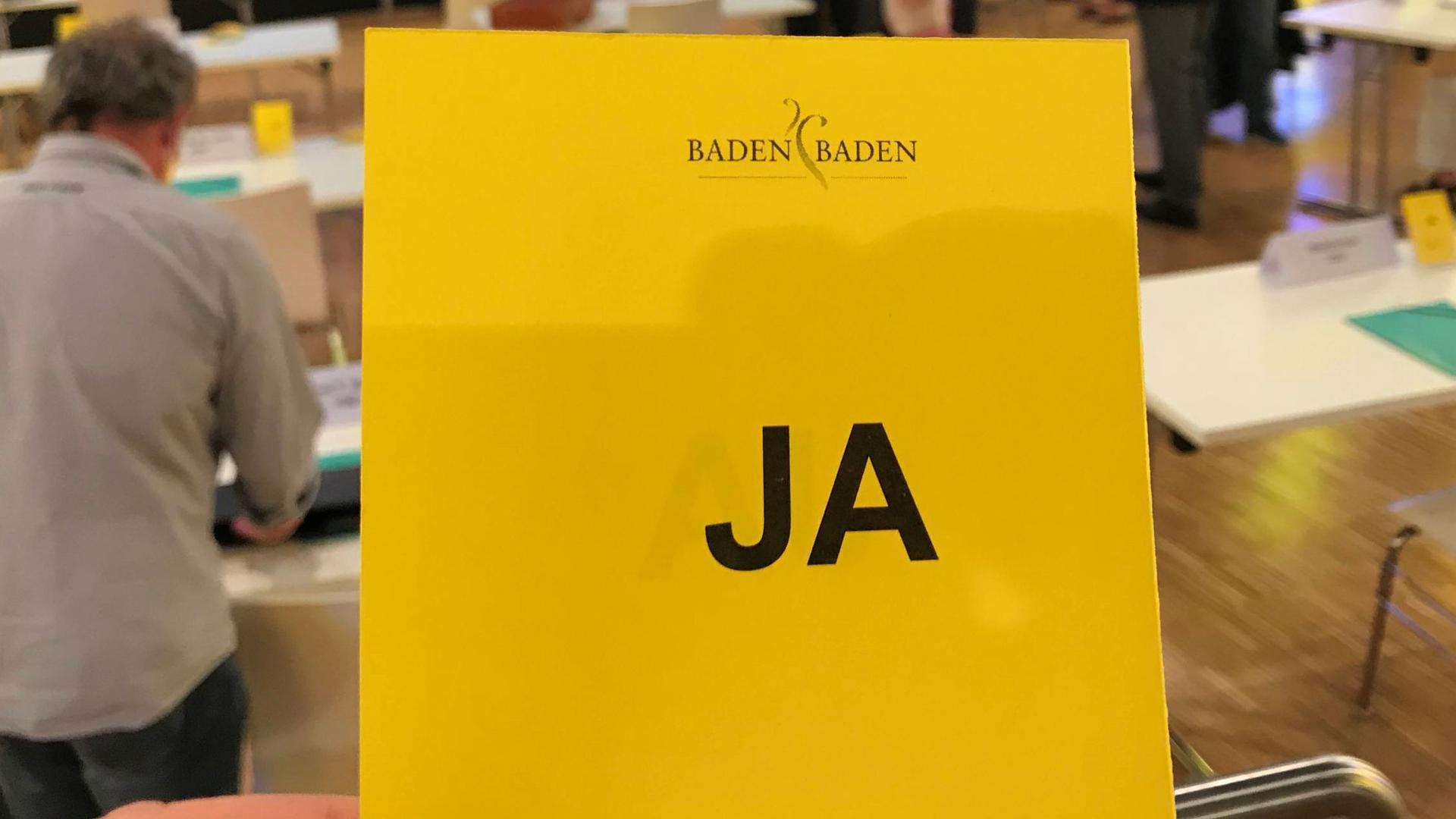 """Mit einer gelben Karte und der Aufschrift """"JA"""" signalisieren Gemeinderäte in Sitzungen in Baden-BadenZustimmung zu einem Tagesordnungspunkt"""