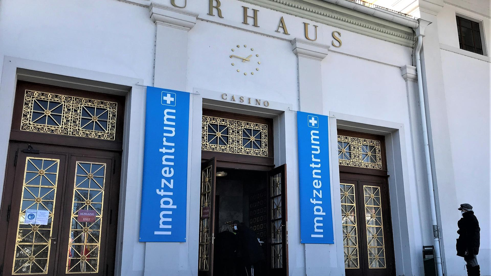 Eine Frau steht am Eingang zum Kurhaus Baden-Baden, das als Impfzentrum dient.
