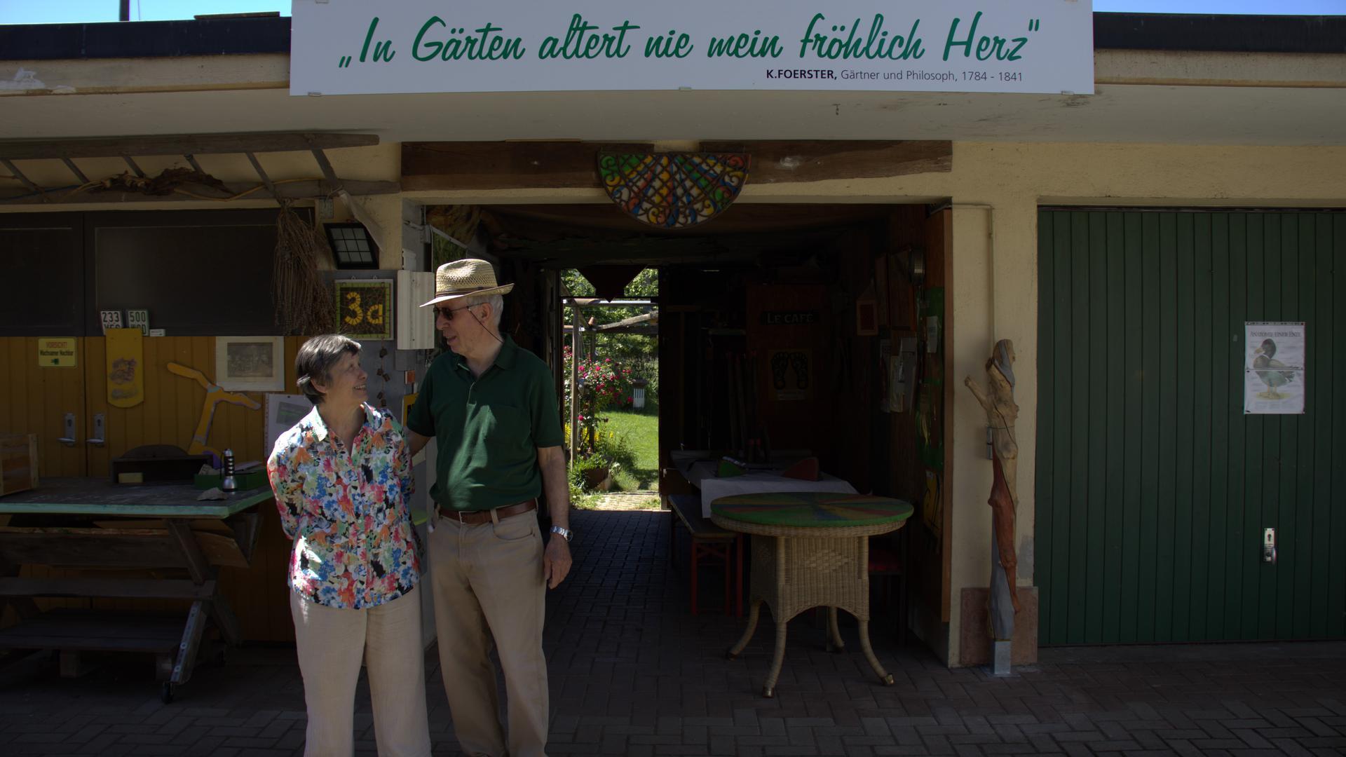 Ein Ehepaar steht vor der Garage und schaut sich dabei an.