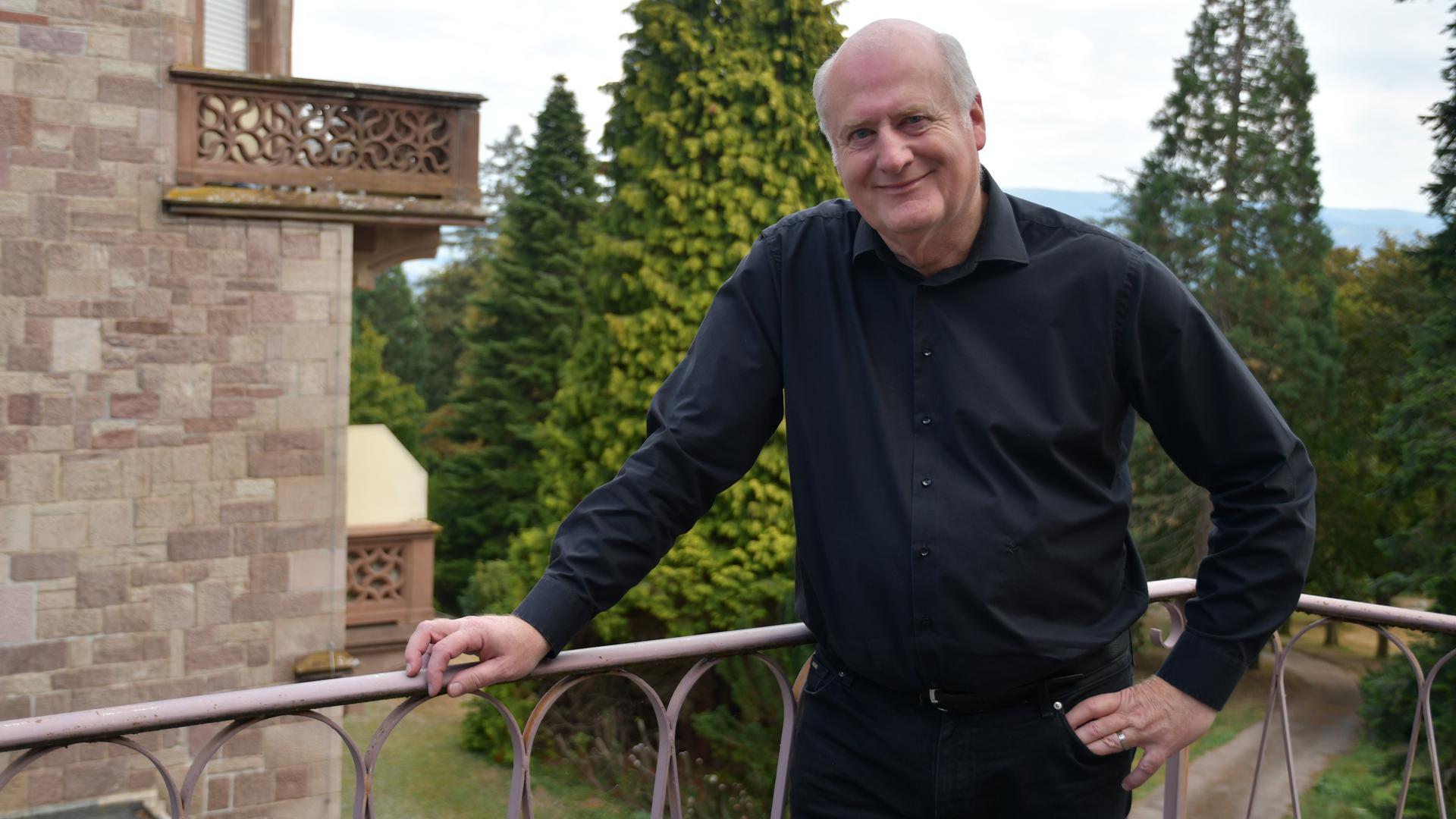 Jürgen Jung steht auf einem Balkon. Im Hintergrund sind Teile der Klinik und Wald zu sehen.