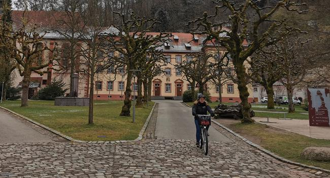 Eine Fahrradfahrerin fährt durch den Innenhof des Klosters Lichtenthal in Baden-Baden.