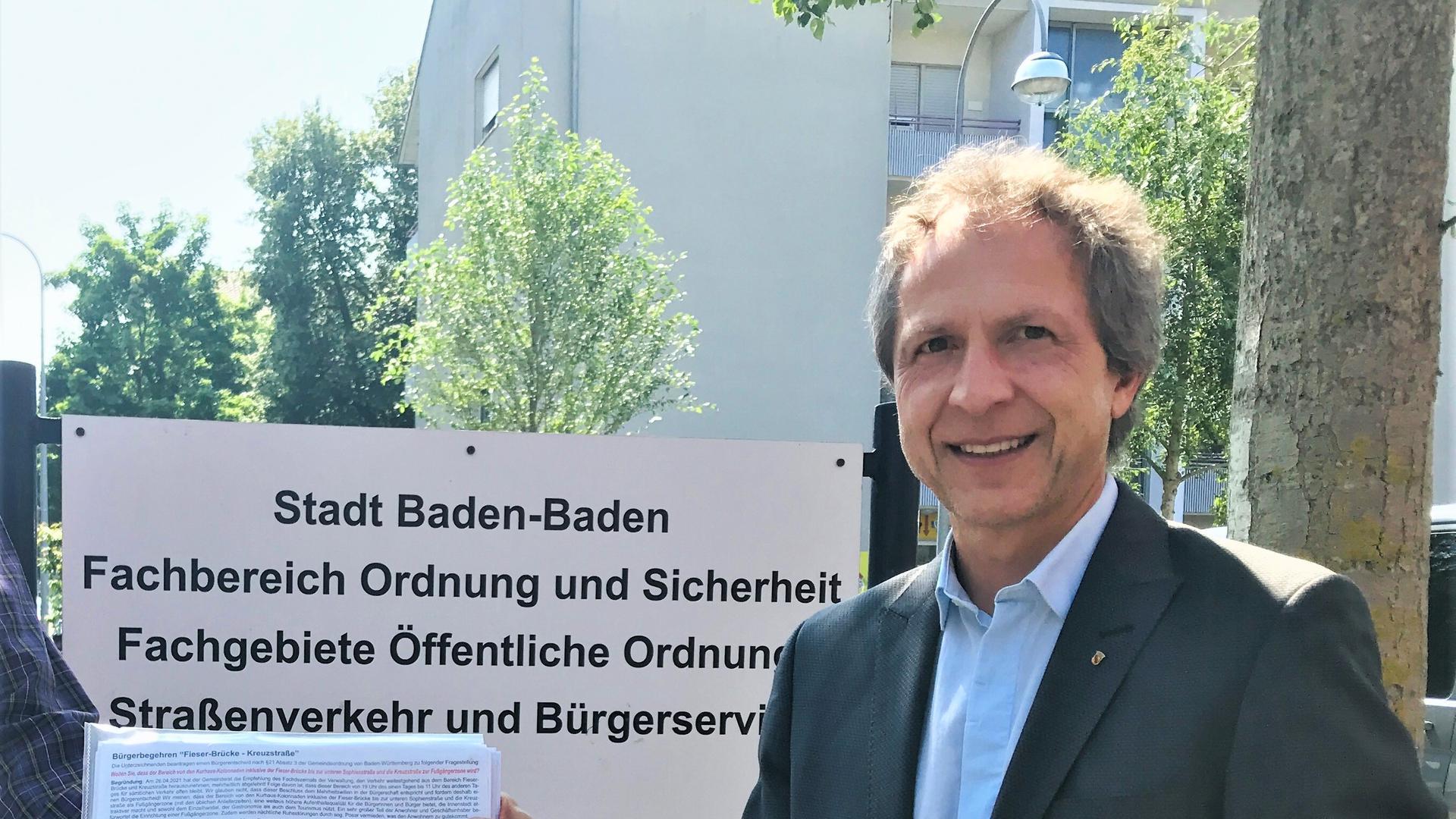 Baden-Badens Bürgermeister Roland Kaiser nimmt eine Unterschriftenliste entgegen.,