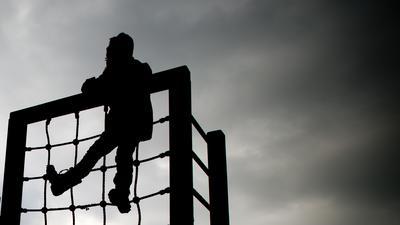 Ein kleines Mädchen hängt oben in einem Klettergerüst.