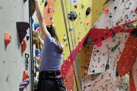 Eine Frau klettert an einer Steilwand in einer Kletterhalle hoch.